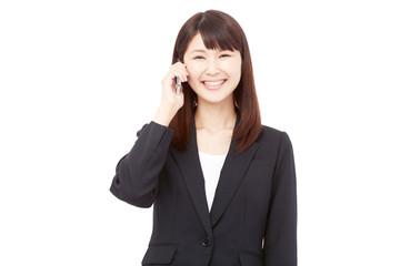 スマートフォンで通話しながら笑うビジネスウーマン