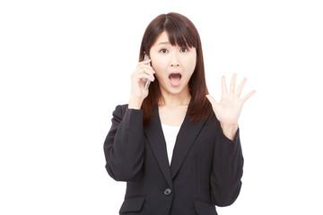 スマートフォンで通話しながら驚くビジネスウーマン