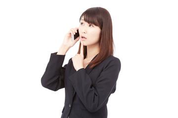 スマートフォンで通話しながら考えるビジネスウーマン