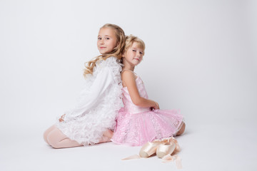 Blonde sisters posing with pointes in studio