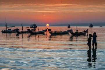Sunset and longtail boats on tropical beach. Ko Tao island, Thai