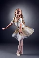 Smiling little ballerina posing looking at camera