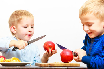 Little boys cutting apple with a kitchen knife