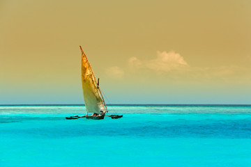 Sailboat (dhow) on the clear turquoise water of Zanzibar island