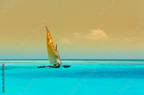 Sailboat (dhow) on the clear turquoise water of Zanzibar island - 73598088