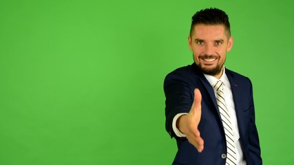 business man gives hand in greeting, smiles - green screen