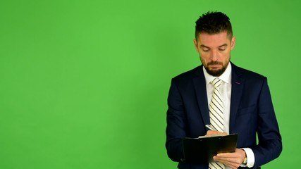 business man writes to paper and smiles - green screen