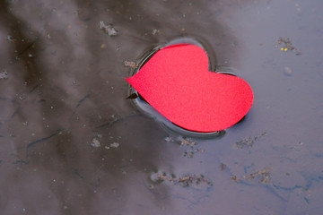 Paper shaped heart in water stream