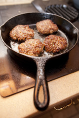 Hot sausage patties cooking in a black cast iron skillet