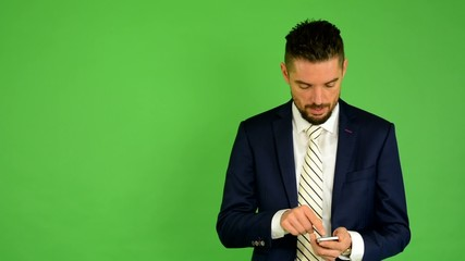 business man works on phone and smiles - green screen - studio