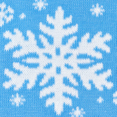 Knitted blue background with snowflakes