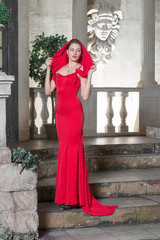 Beautiful girl in a red dress in an old castle