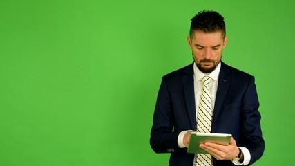 business man works on tablet - green screen - studio
