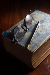 Eyeglasses and pen on antique book.