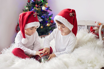 Two cute adorable boys enjoying candies at christmas time