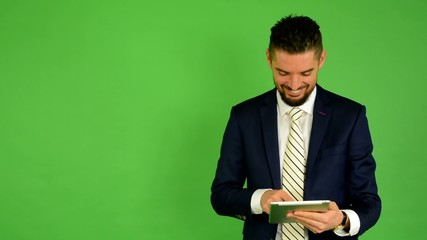 business man works on tablet and smiles - green screen - studio