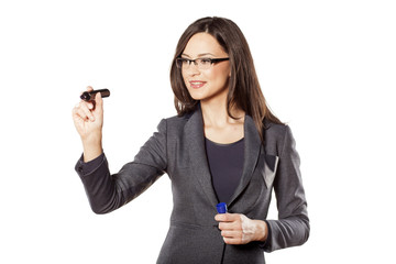 smiling businesswoman writing with a marker in the empty space