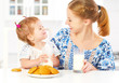 happy family mother and girl at breakfast: biscuits with milk