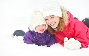 happy family mother and baby daughter playing in winter snow