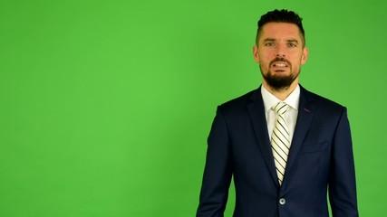 business man talks to camera (interview) - green screen - studio