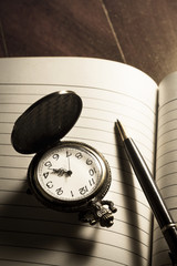 Pocket watch and pen on book.