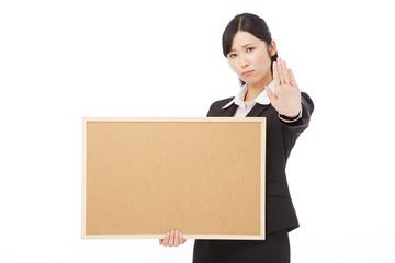 メッセージボードを持って制止するビジネスウーマン