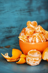 Sweet tangerines and oranges on table on wooden background