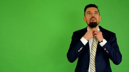 business man adjusts his tie - green screen - studio