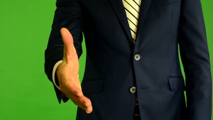 business man gives a hand in greeting - green screen - closeup