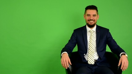 business man sits and smiles - green screen - studio