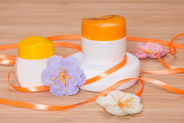 Jars of cream with flowers and satin ribbon