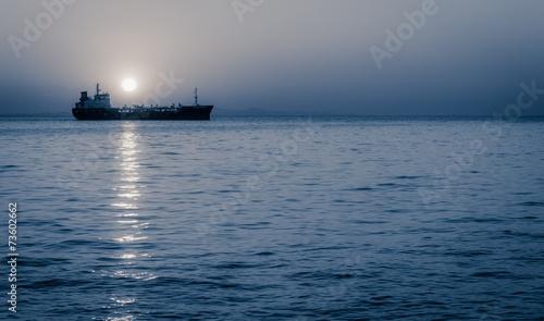 Moon rising above a sailing cargo ship - 73602662