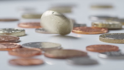 UK One Pound coin spinning amongst other coins in slow motion