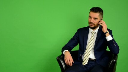 business man sits and phone - green screen - studio
