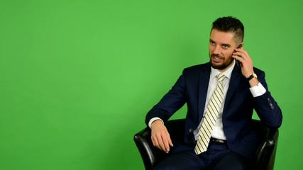 business man sits and phone and smiles - green screen