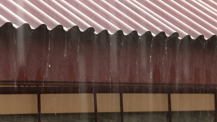 rain pours with a metal roof on a background of the plastic wind
