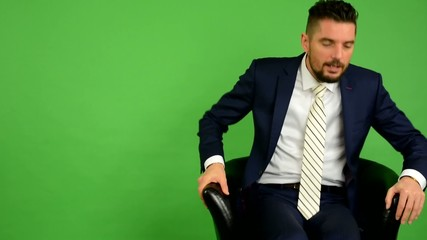 business man goes to sit down and smiles - green screen - studio