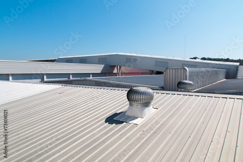 Architectural detail of metal roofing on commercial construction - 73604021