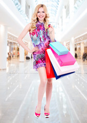 Woman with purchasing in pink dress  in the big mall