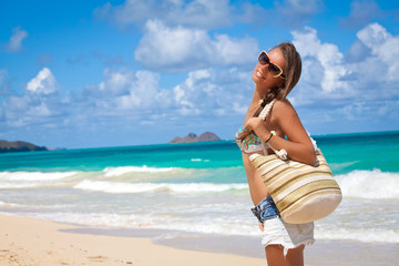 Tourist woman relaxing on tropical beach in Hawaiian peacefully.