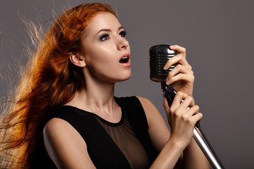 Singing woman on grey background