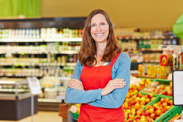 Lächelnde Marktleiterin steht im Supermarkt