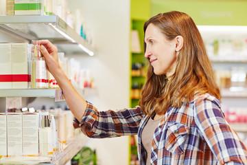 Ältere Frau kauft Kosmetik in Drogerie