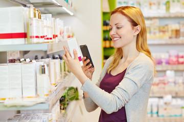 Frau beim Preisvergleich mit Smartphone im Supermarkt