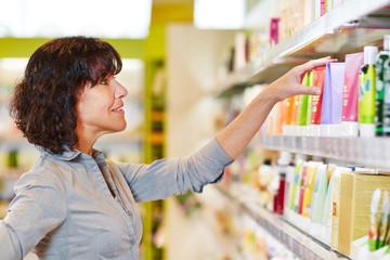 Frau trifft Entscheidung beim Shopping in Drogerie