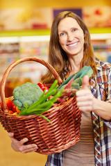 Frau mit Korb voller Gemüse hält Daumen hoch
