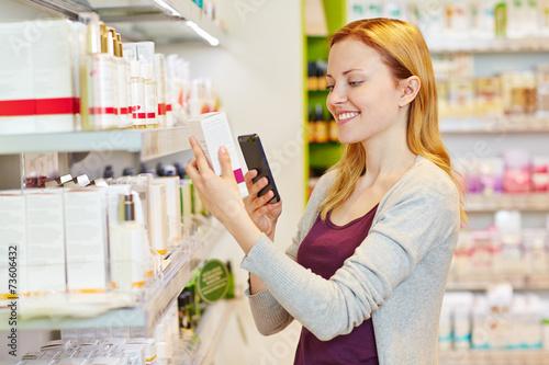 Frau beim Preisvergleich mit Smartphone im Supermarkt - 73606432