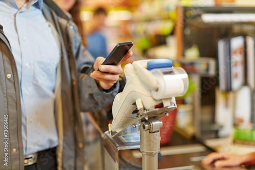 Leinwandbild Motiv Mann zahlt mit Smartphone an Kasse im Supermarkt