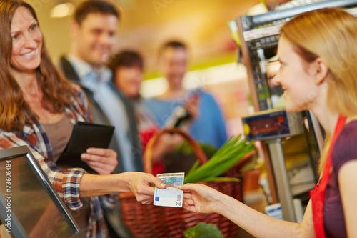 Leinwanddruck Bild Frau zahlt mit Euroschein an Kasse im Supermarkt
