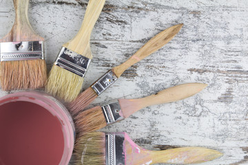 Paintbrushes and paint can in a wood background